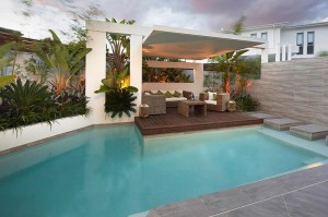 Custom-Pool-Area-undercover-patio-lounge-with-garden-beds-and-palms