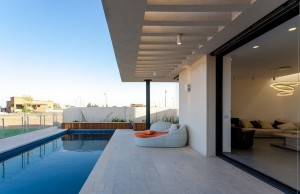 Modern-Simple-Pool-Family-Home-pool-terrace-with-stone-tile-floor-and-rectangular-openings-flat-roof-also-outdoor-daybed-and-large-sliding-glass-door